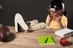 smiling schoolboy in american football helmet sitting with legs on table with ball books apple and textbook on grey