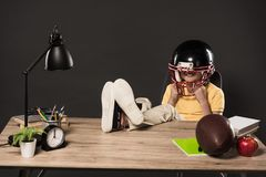 smiling schoolboy in american football helmet sitting with legs on table with ball books plant lamp colour pencils apple