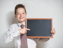 Smiling schoolboy with empty black chalkboard Stock Photos
