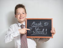 Smiling schoolboy with empty black chalkboard Stock Photo