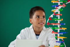 Smiling schoolboy experimenting molecule model in laboratory Stock Photo