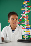 Smiling schoolboy experimenting molecule model in laboratory Stock Images
