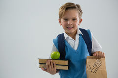 Smiling schoolboy holding books and lunch paper bag. Against white background Stock Photo
