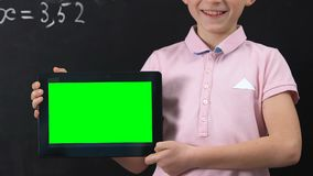 Smiling schoolboy holding tablet PC wit green screen, online education concept