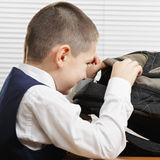 Smiling schoolboy looking into backpack Royalty Free Stock Image