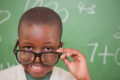 Smiling schoolboy looking over his glasses Stock Images