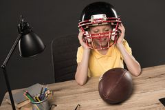 smiling schoolboy putting on american football helmet at table with ball lamp colour pencils and books on grey