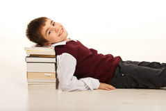 Smiling schoolboy resting head on books Royalty Free Stock Images