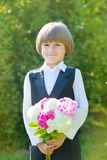 Smiling schoolboy in school uniform with flowers Stock Photography
