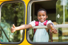 Smiling schoolboy showing thumbs up from bus Stock Photos