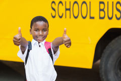 Smiling schoolboy showing thumbs up in front of school bus Stock Image