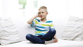 Smiling schoolboy with smartphone at home Royalty Free Stock Images