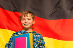 Smiling schoolboy standing next to flag of Germany Royalty Free Stock Images