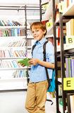Smiling schoolboy stands and holds books Royalty Free Stock Photography