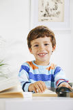 Smiling schoolboy studying in home. Royalty Free Stock Photography