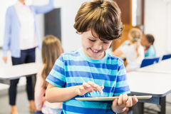 Smiling schoolboy using digital tablet in classroom. At elementary school Stock Photo