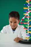 Smiling schoolboy using digital tablet in laboratory. At school Stock Images
