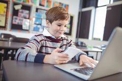 Smiling schoolboy using laptop and mobile phone on desk at classroom Royalty Free Stock Photos