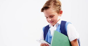 Schoolboy using mobile phone against white background. Smiling schoolboy using mobile phone against white background stock footage