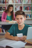 Smiling schoolboy using mobile phone in library at school. Portrait of smiling schoolboy using mobile phone in library at school Royalty Free Stock Photography