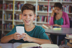 Smiling schoolboy using mobile phone in library at school. Portrait of smiling schoolboy using mobile phone in library at school Royalty Free Stock Photo