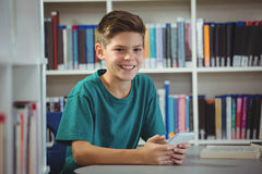 Smiling schoolboy using mobile phone in library at school. Portrait of smiling schoolboy using mobile phone in library at school Royalty Free Stock Image