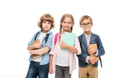 Schoolchildren with backpacks and books. Smiling schoolchildren with backpacks and books, isolated on white Stock Photo