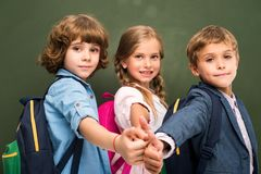 Schoolchildren showing thumbs up. Smiling schoolchildren showing thumbs up, chalkboard behind Stock Photography