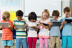Smiling schoolchildren using digital tablet Royalty Free Stock Photography
