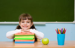 Smiling schoolgirl in the classroom on the background of chalkboard Royalty Free Stock Photos