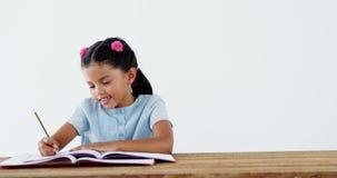 Smiling schoolgirl doing her homework stock video footage