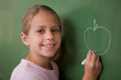 Smiling schoolgirl drawing an apple Royalty Free Stock Images