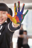 Smiling schoolgirl finger painting, close up on hand Stock Image