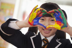 Smiling schoolgirl finger painting, close up on hands stock image