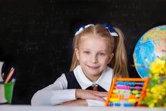 Schoolgirl with globe near school blackboard Royalty Free Stock Images