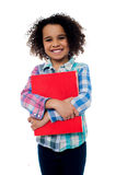 Smiling schoolgirl holding a book Stock Photo