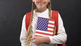 Smiling schoolgirl holding book with USA flag, English language studying. Stock footage stock video footage