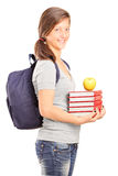 A smiling schoolgirl holding books and green apple Stock Photos