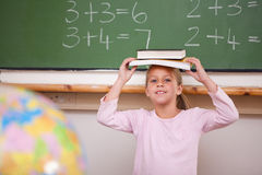 Smiling schoolgirl holding her book on her head stock photography