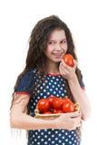 Smiling schoolgirl holds basket of tomato Stock Photo