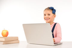 Smiling schoolgirl with laptop. Smiling schoolgirl sitting at desk with laptop Royalty Free Stock Images