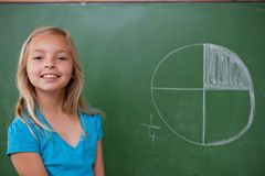 Smiling schoolgirl learning the divisions. On a blackground stock photos
