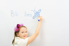 Smiling schoolgirl learning to write letter B. In front of board Royalty Free Stock Image