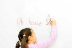 Smiling schoolgirl learning to write letter H. In front of board Stock Image