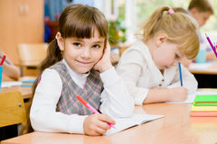 Smiling schoolgirl looking at camera during lesson Stock Photos