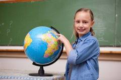 Smiling schoolgirl looking at a globe Stock Images