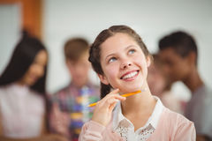 Smiling schoolgirl looking up in classroom. At school Royalty Free Stock Images
