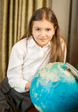 Smiling schoolgirl posing with Earth globe at cabinet Stock Photo