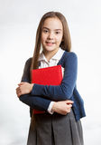 Smiling schoolgirl posing with red book against isolated backgro Stock Image