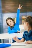 Smiling schoolgirl raises hand